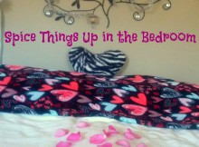 bed with a heart pillow and rose petals