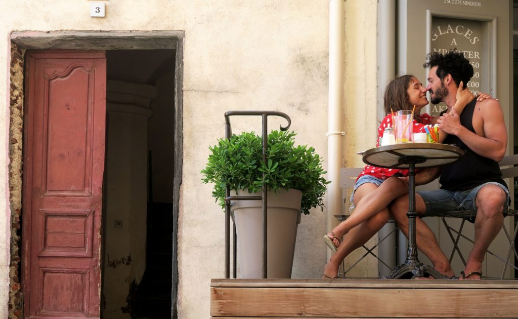 couple sitting at a bistro table kissing