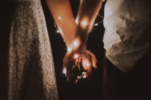 Couple holding hands with lights wrapped around them